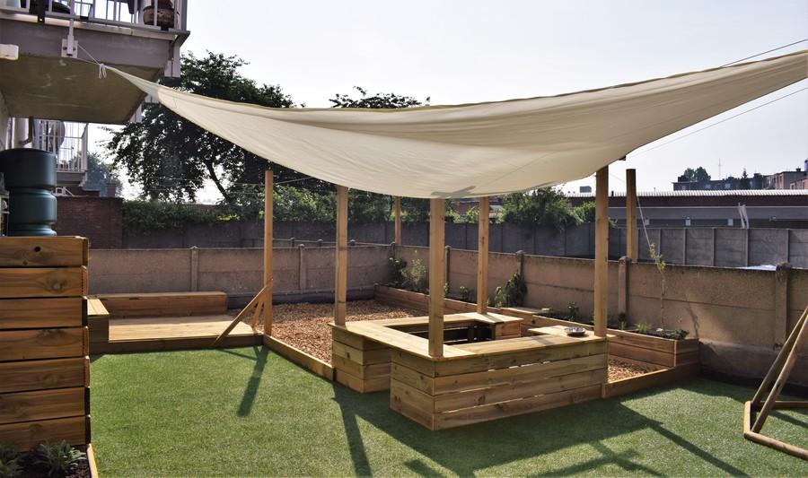 Een overzicht van de nieuwe buitenruimte met buitenkeuken, houtsnipperzone en zitpodium.