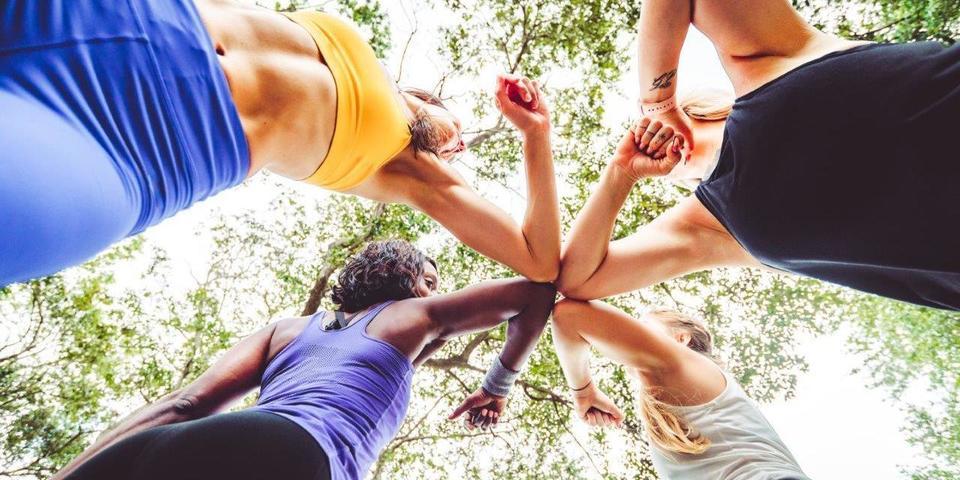 Een groep jonge vrouwen start hun sportsessie door elkaar een elleboogje te geven.