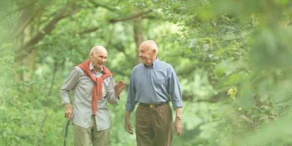 Twee oudere mannen praten en wandelen samen door een bos.
