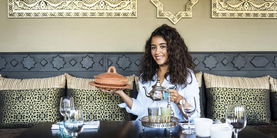 Vrouw met kan thee en schotel in de handen