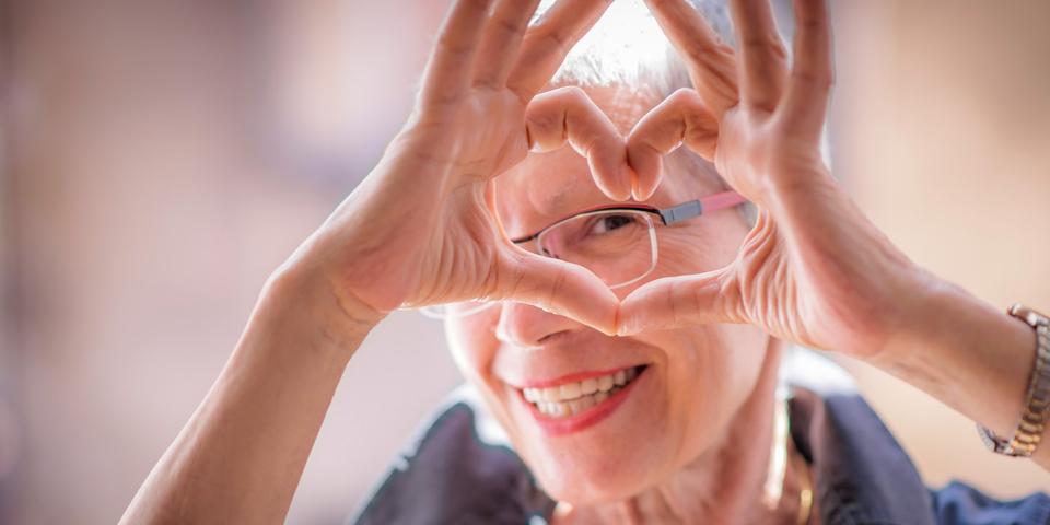 Oudere dame die een hartje vormt met haar handen