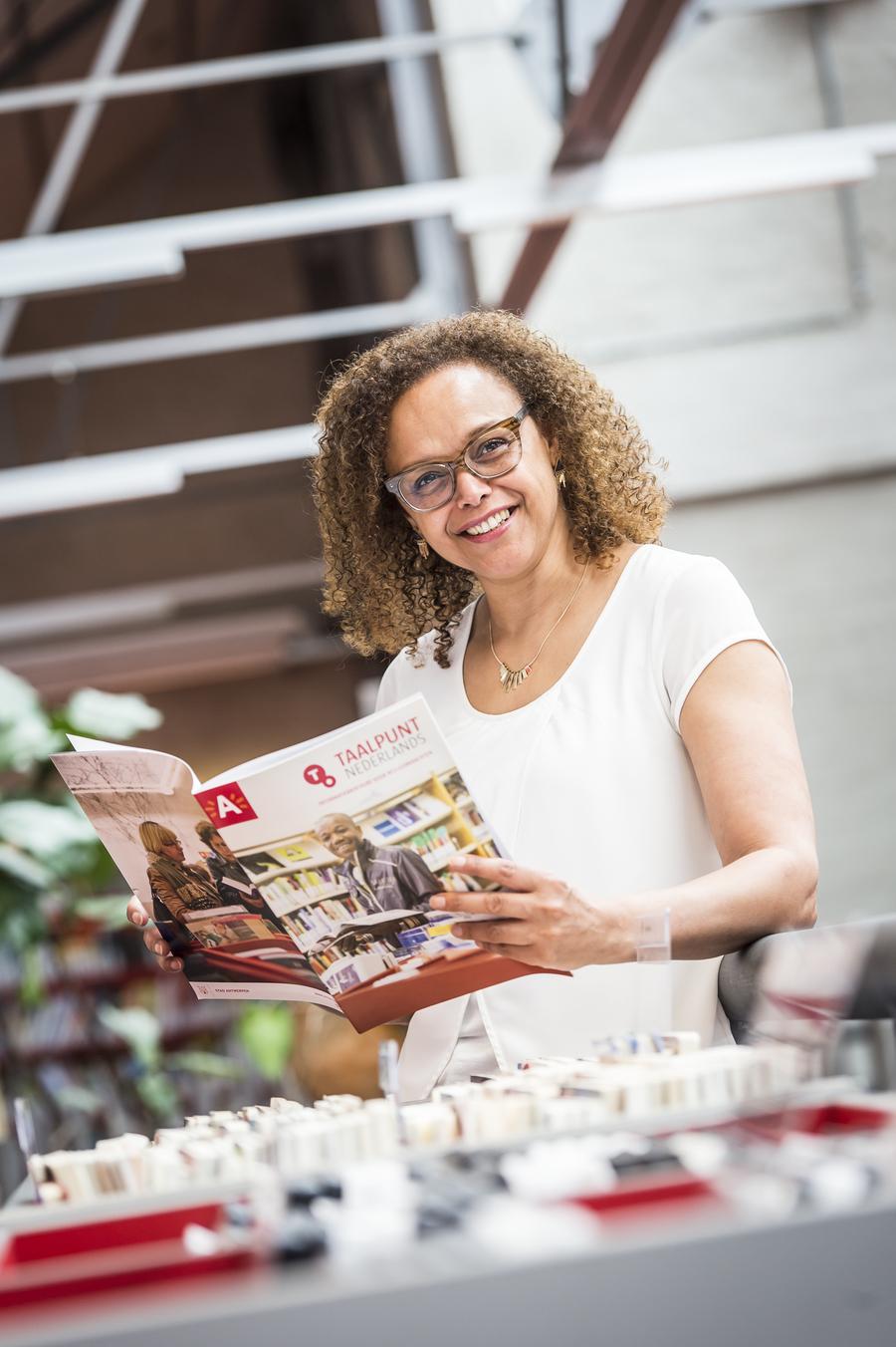 Brigitte poseert met een brochure Taalpunten voor docenten.
