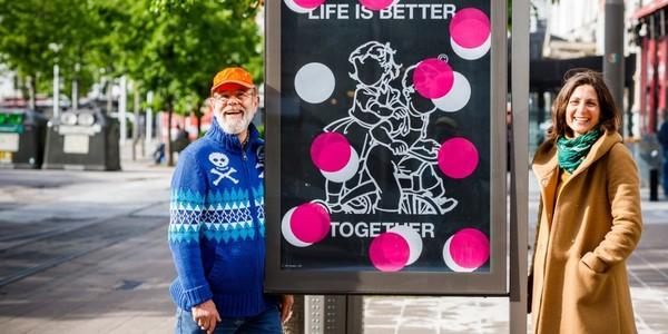 2 kunstenaars poseren aan een billboard met kunstaffiche.