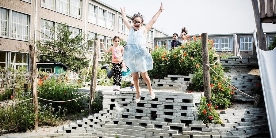 Meisje springt van heuvel op schoolspeelplaats