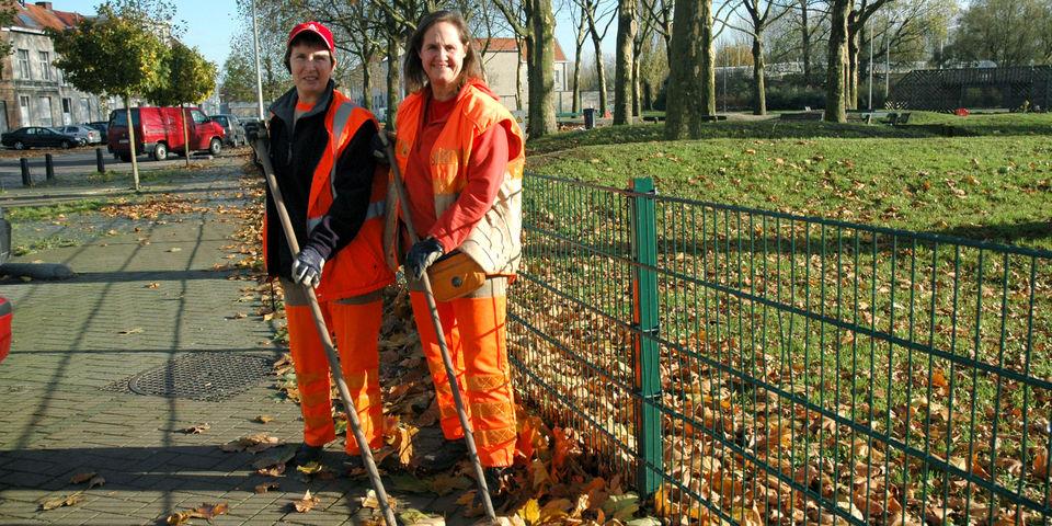 Stadsmedewerkers vegen bladeren op