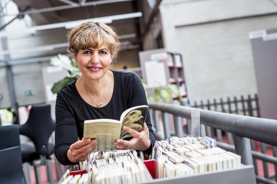 Parvin poseert met een Makkelijk lezen-boekje in het Taalpunt van Permeke.