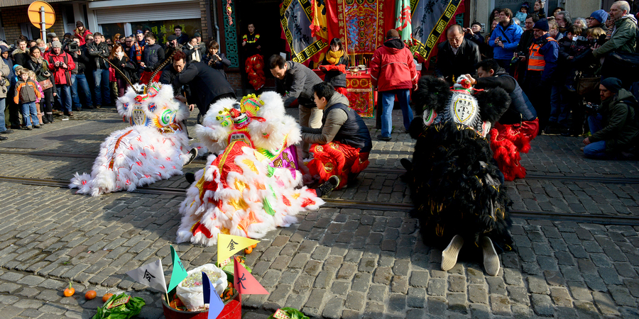Veel mensen kijken naar een parade van Chinese draken en leeuwen.