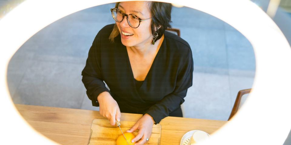 Lina snijdt een appelsien op tafel, het beeld werd genomen door de opening van een ledlamp aan het plafond.