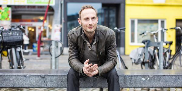 Stadsdichter Stijn Vranken op een bank op het De Coninckplein