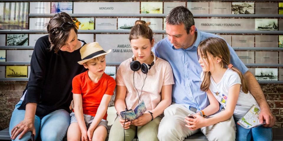 Een mama, papa, en hun drie dochters bekijken samen een smartphone.