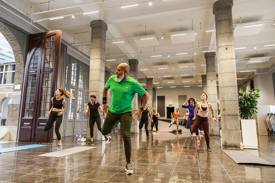 een groep mensen doet een workout in de inkomhal van het Havenhuis