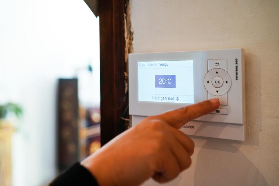 Een hand stelt de temperatuur op de kamerthermostaat bij tot 20 graden Celcius.