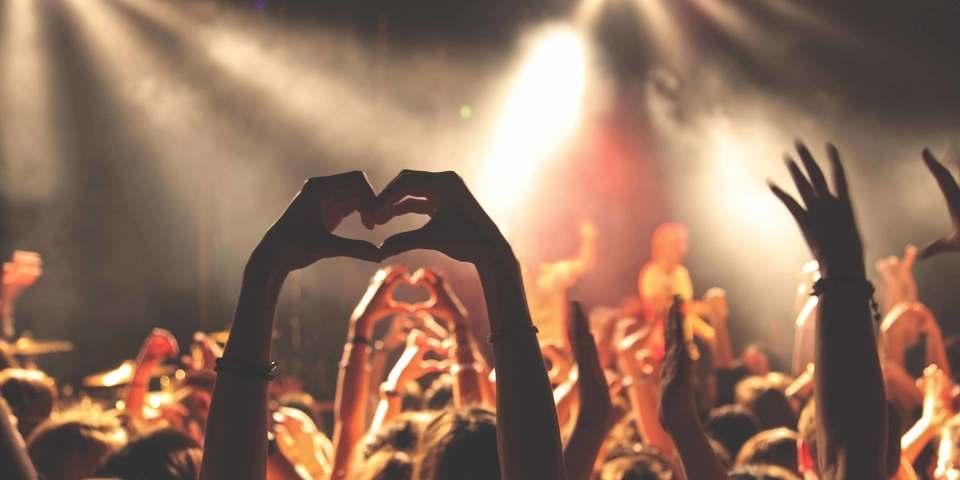 Een bezoeker vormt een hart met haar handen tijdens een concert.