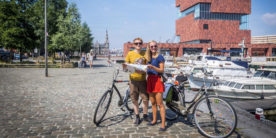 Een man en een vrouw staan naast hun fietsen met een kaart in de hand. Op de achtergrond het MAS.