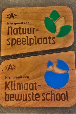 """Twee schoolpoortborden uit hout. Op de ene staat """"hier groeit een natuurspeelplaats"""" en op de andere """"hier groeit een klimaatbewuste school""""."""