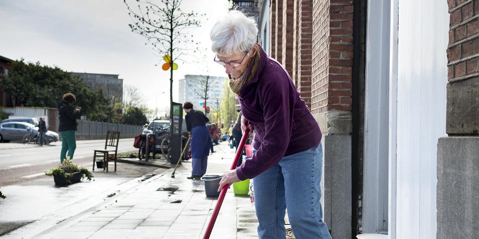 Oudere dame poetst voor haar eigen voordeur met buren op de achtergrond.
