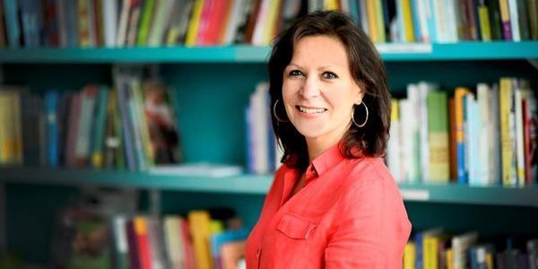 Projectleider Marijke Cassiers staat voor een boekenrek.