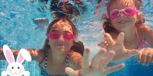 Twee meisjes duiken naar iets buiten het beeld