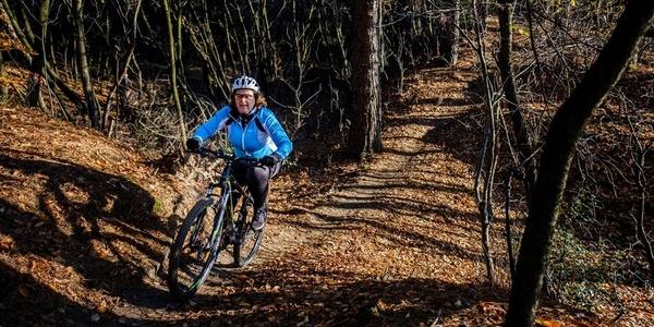 Een vrouw rijdt op een mountainbike in het bos