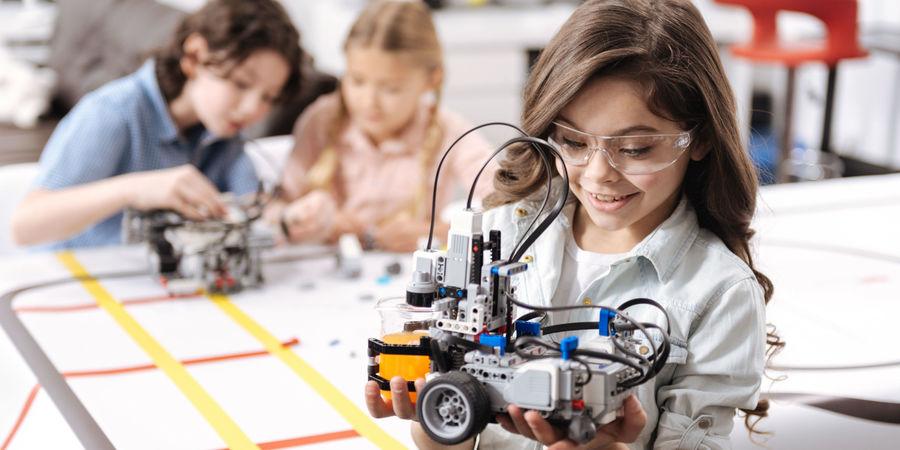 Een meisje toont trots het resultaat van haar Lego Mindstorm.