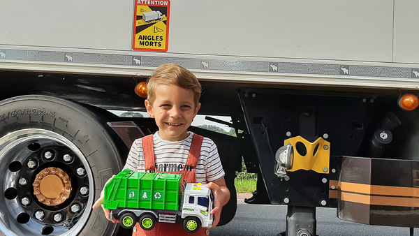 Kind staat met speelgoedvrachtwagen voor een grote vrachtwagen.