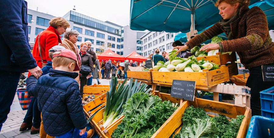 mensen kopen groenten op de markt