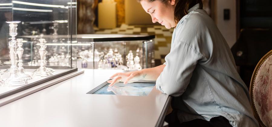 Een vrouw scrolt over een tablet in diamantmuseum DIVA.