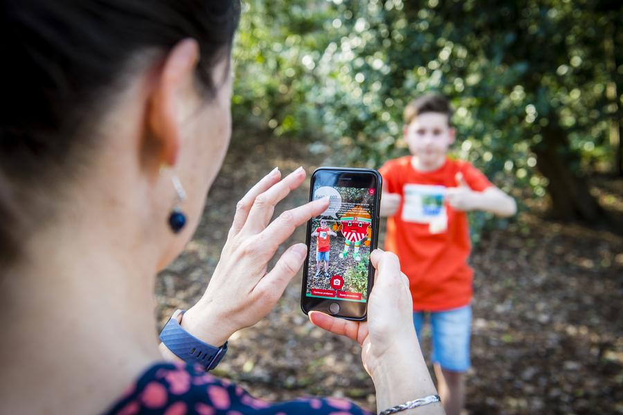Een jongetje poseert in het park. Zijn mama neemt een foto met haar GSM. Op het scherm van de GSM zie je het jongetje en Antwan, de mascotte van Sporting A