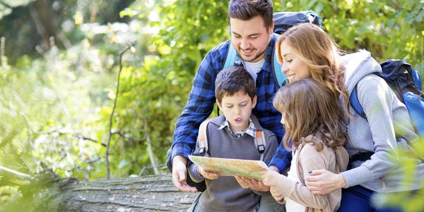 Een familie kijkt op een wandelkaart in de natuur