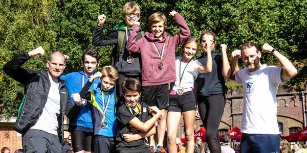 Deelnemers aan Run4Freedom tonen hun medaille