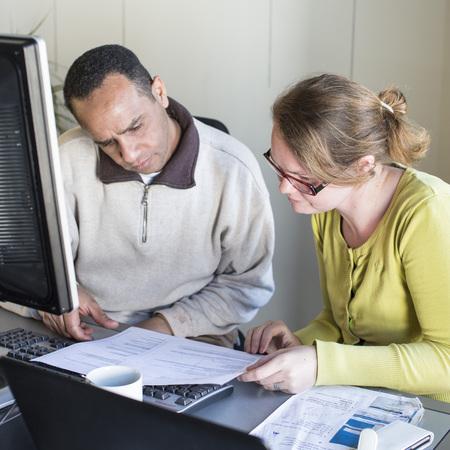 Leden van een vereniging werken met de computer in een buurtsecretariaat.
