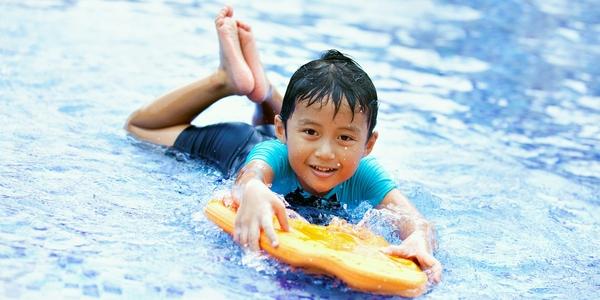 Jongen in het water met een plank