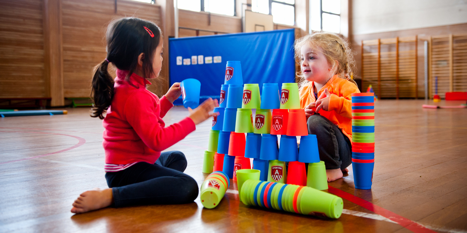 Twee meisjes bouwen een toren met stapelbekers