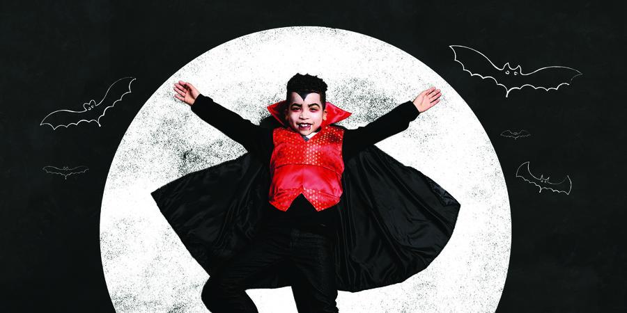 Kind verkleedt als Dracula met volle maan op achtergrond