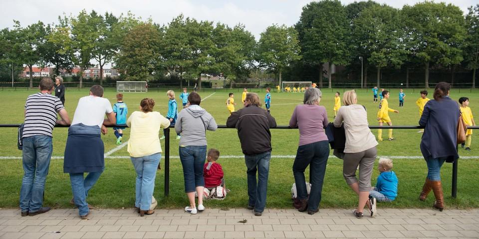 Ouders kijken naar voetbalmatch