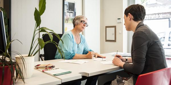 Medewerkster van een woonkantoor geeft advies aan een bezoekster