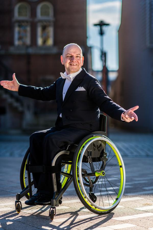 Marcel poseert lachend met smoking aan in een rolstoel