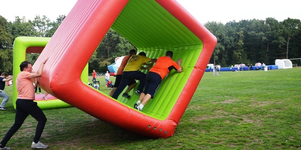 Stormgames-deelnemers verplaatsen zich in een opblaasbare kubus over een veld.