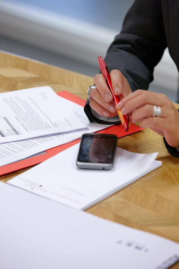 Persoon aan tafel met smartphone en documenten