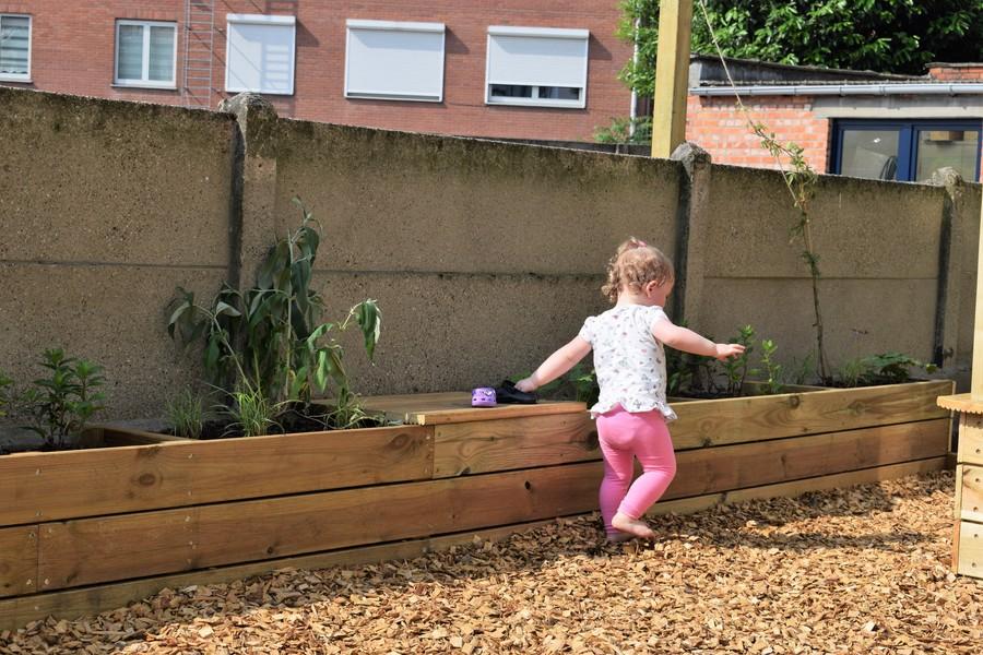 Meisje loopt over houtsnippers met blote voetjes