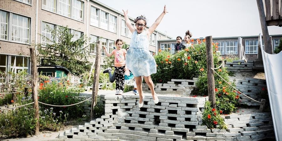 Een meisje springt van een speelheuvel