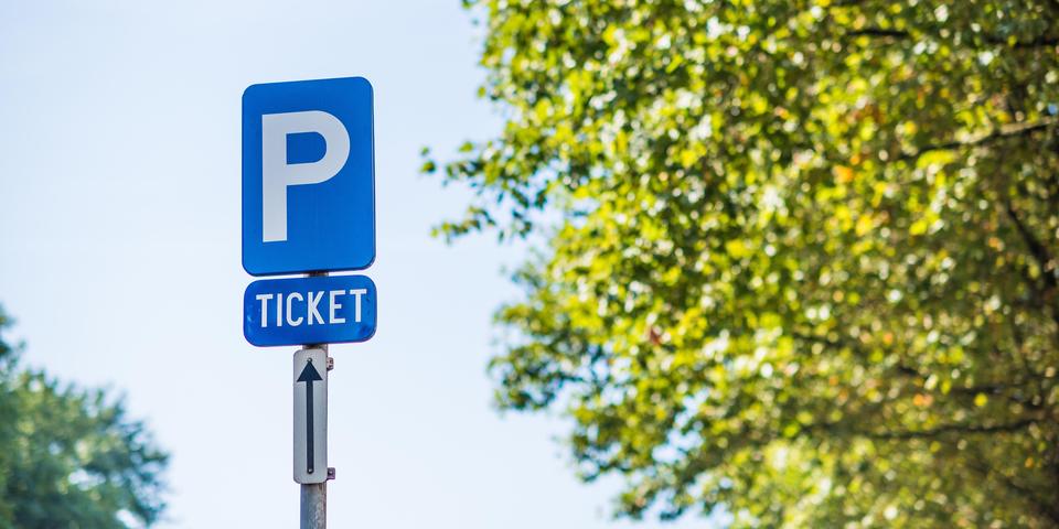 Foto van een bauw verkeersbord met een witte P erop