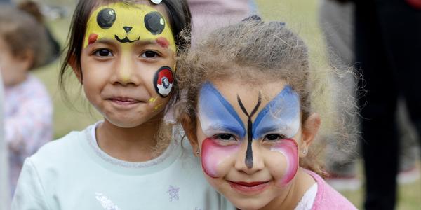 Twee meisjes gescminkt als een vlinder kijken in de camera.