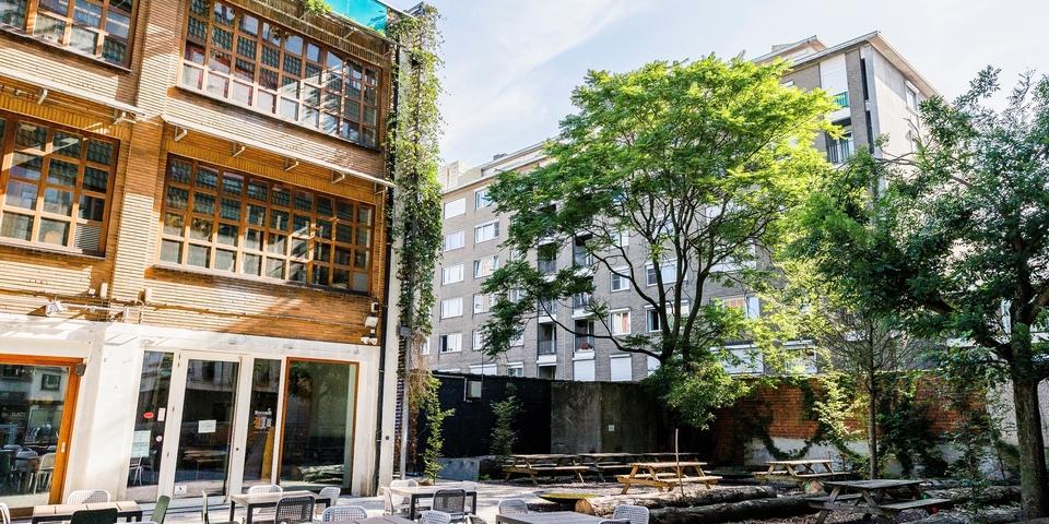 We zien het voorplein van het EcoHuis, met het terras en picknicktafels en veel groen.