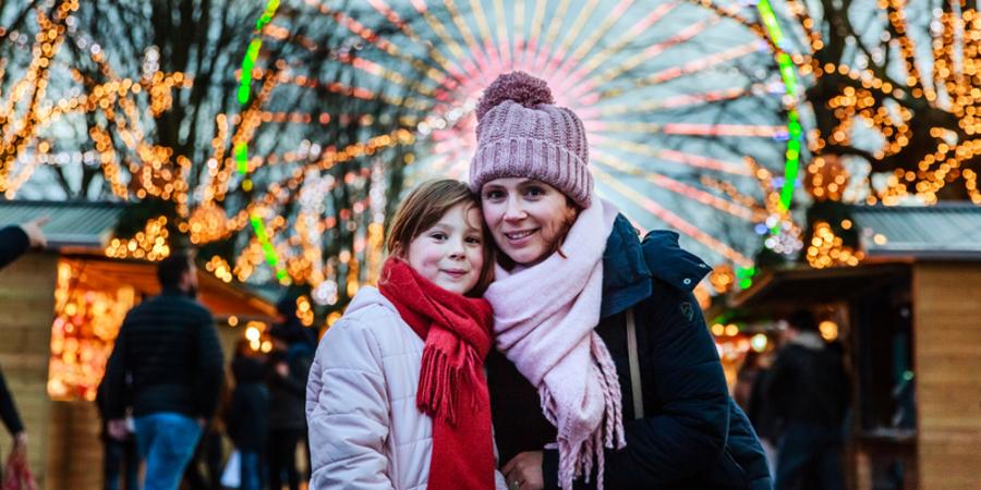 Vrouw en kind op de kerstmarkt met reuzenrad