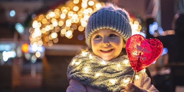 Klein meisje met grijze muts en sjaal houdt hartjeslolly vast