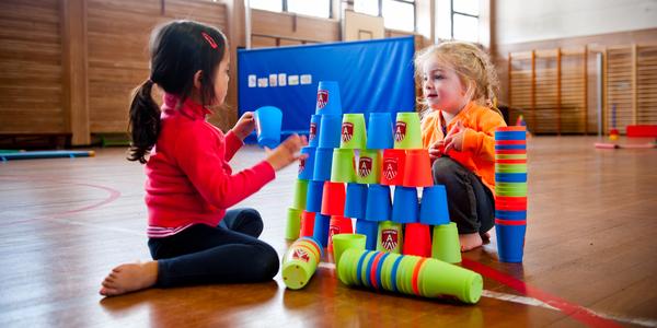Twee meisjes maken een toren met stapelbekers