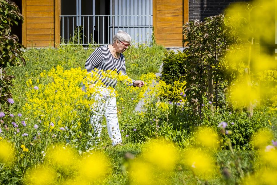 Vrouw wandelt door kleurige beplanting in de tuin.
