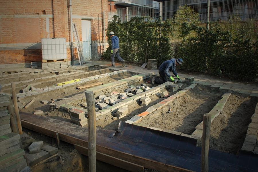 Met de oude stenen worden de verhoogde moestuinbakken gebouwd.