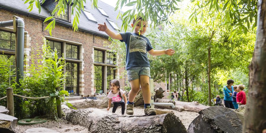 Jongen balanceert over boomstam